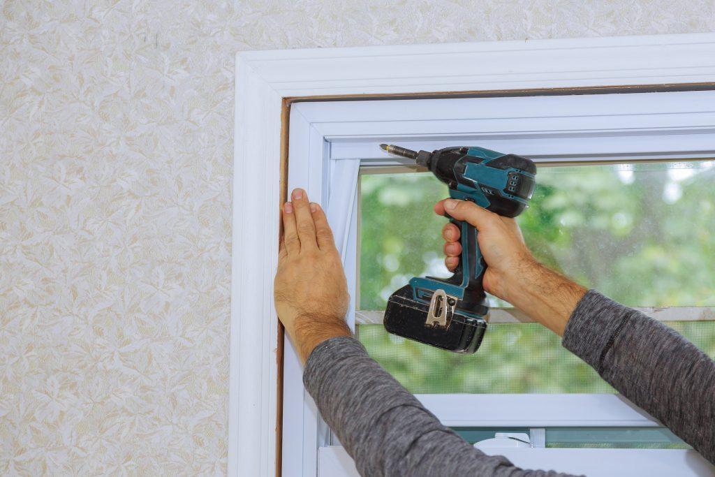 Process of worker installing new plastic pvc window man using a screwdriver
