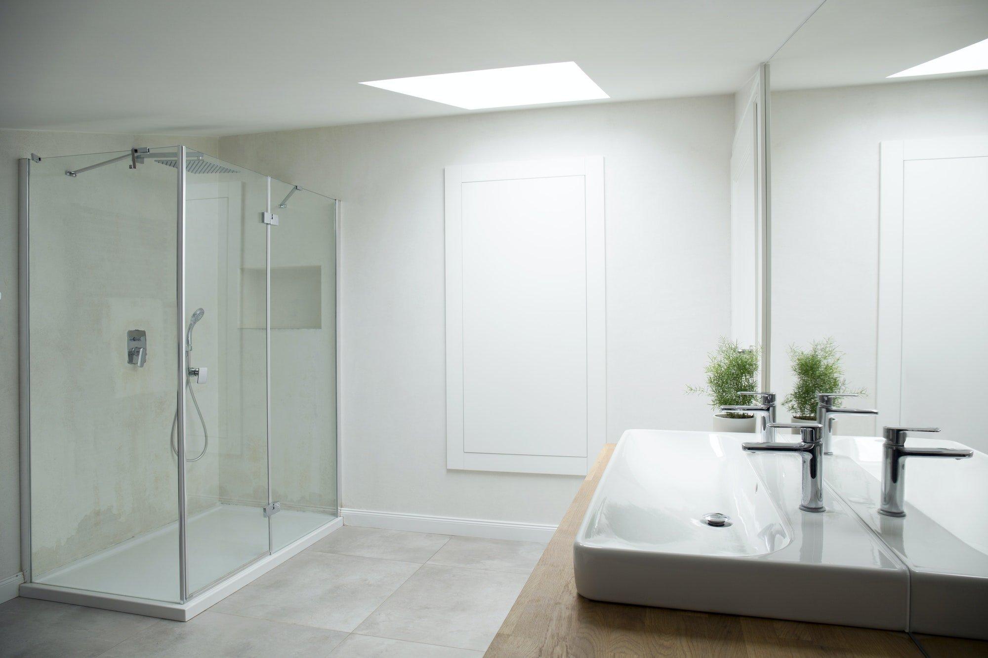 Interior de baño blanco con ventana de aluminio